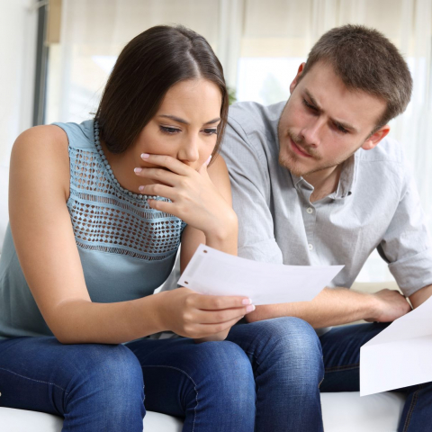 Couple looking worried about a bill